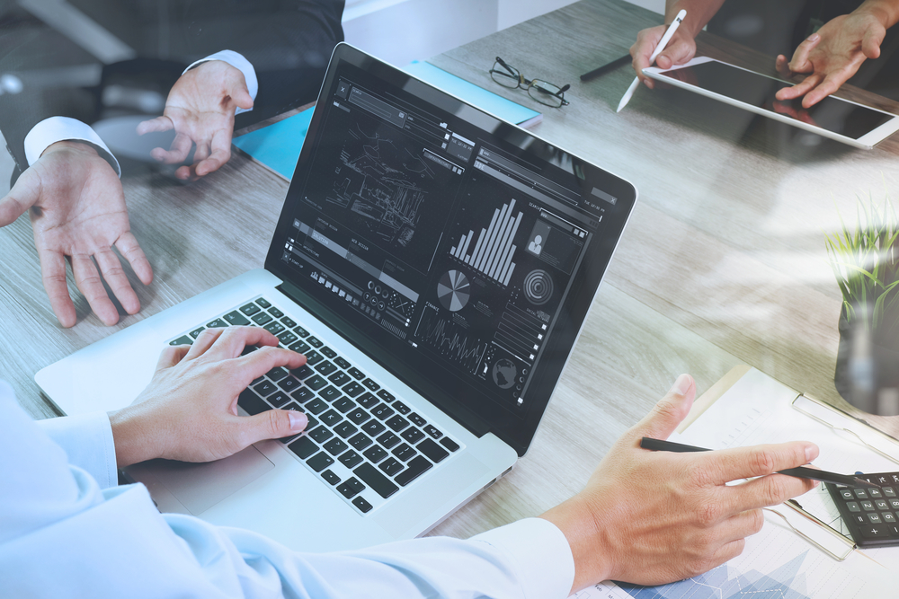 business documents on office table with smart phone and laptop computer and graph financial with social network diagram and three colleagues discussing data in the background-1